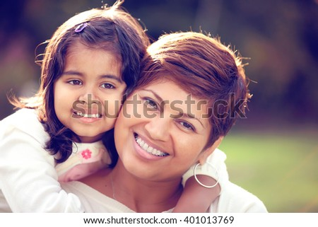 Portrait of a happy Hispanic mother and daughter at the park - stock photo