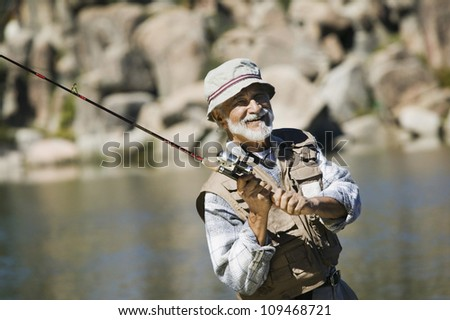 Portrait of a happy Hispanic senior man fishing on a sunny day