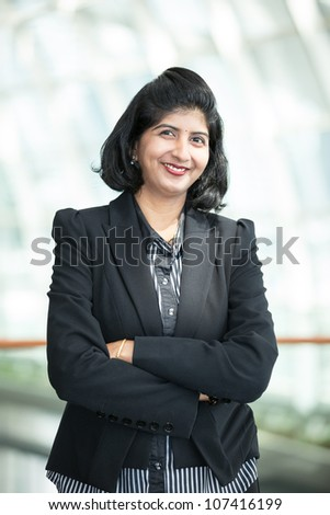 Portrait of a happy Indian business woman standing with folded arms. - stock photo