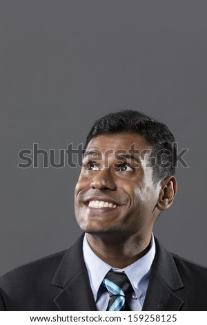 Portrait of a happy Indian businessman looking upwards. Dark grey background. The photo has been composed so there is plenty of space for your message. - stock photo