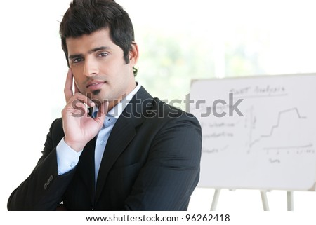 portrait of a happy Indian businessman standing in the boardroom with his colleague in the background - stock photo
