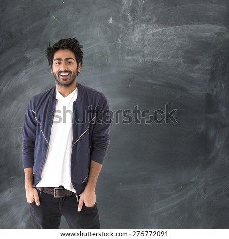 Portrait of a happy Indian man standing next to a blackboard. - stock photo