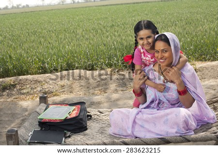 Portrait of a happy Indian mother and daughter sitting on cot with field in background - stock photo