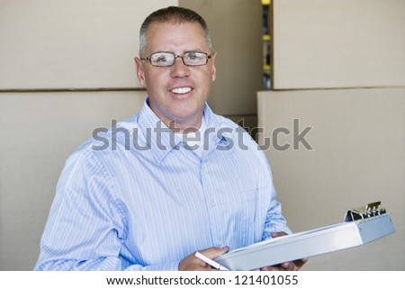 Portrait of a happy industrial supervisor holding clipboard with cardboard boxes in the background