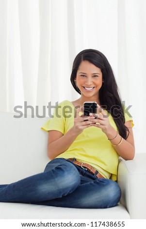 Portrait of a happy Latino looking her smartphone while sitting on a sofa