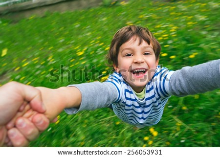 Portrait of a happy, laughing boy being held and spun around in the garden with yellow flowers background - stock photo