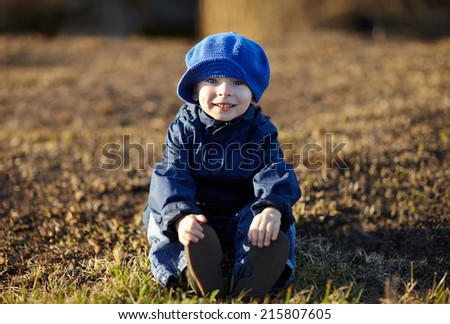 Portrait of a happy laughing little boy sitting on the ground in autumn park - stock photo
