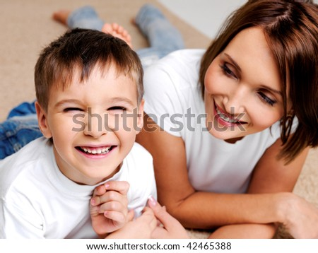 Portrait of a happy laughing preschooler boy with his pretty young mother lying  on the floor - stock photo