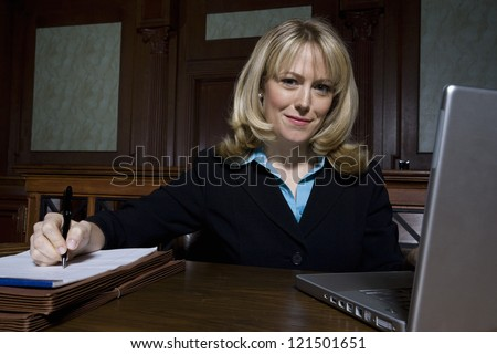 Portrait of a happy lawyer writing notes with laptop in the foreground - stock photo