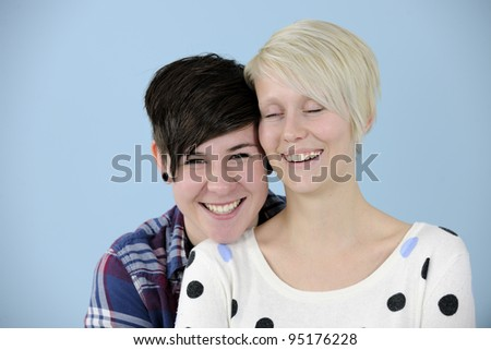 portrait of a happy lesbian couple on blue background - stock photo