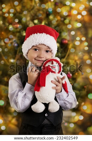 portrait of a happy little boy holding a new gift. boy in a hat of Santa with a gift - stock photo