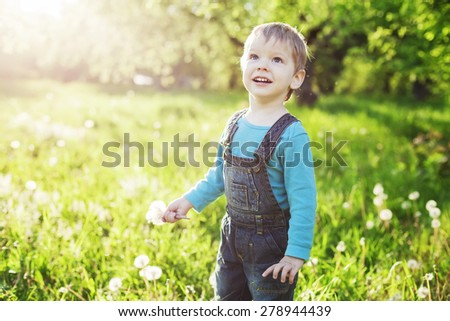 Portrait of a happy little boy holding dandelions and looking up - stock photo