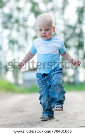 Portrait of a happy little boy in the green nature park. Outdoor - stock photo