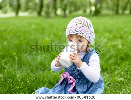 Portrait of a happy little girl drinking milk in the park