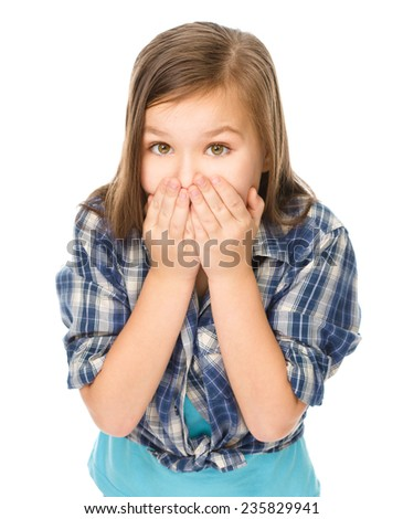 Portrait of a happy little girl laughing, covering her mouth with hands, isolated over white - stock photo