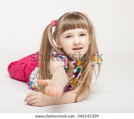 Portrait of a happy little girl lying on the floor