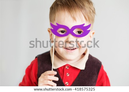 Portrait of a happy little kid with funny paper glasses against a white background - stock photo
