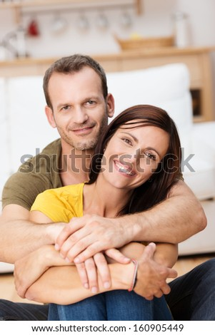 Portrait of a happy loving adult couple with the man embracing the woman from behind - stock photo