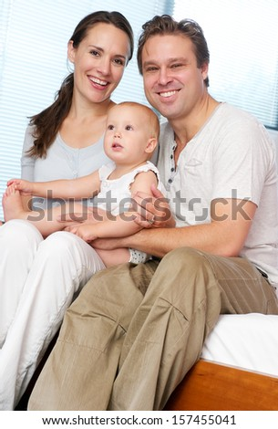 Portrait of a happy loving couple holding cute baby at home