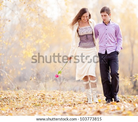 portrait of a happy loving couple walking  outdoor in the autumn park - stock photo