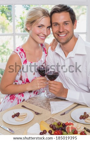 Portrait of a happy loving young couple with wine glasses at dining table at home - stock photo