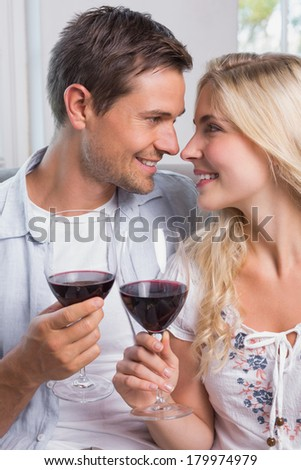 Portrait of a happy loving young couple with wine glasses at home