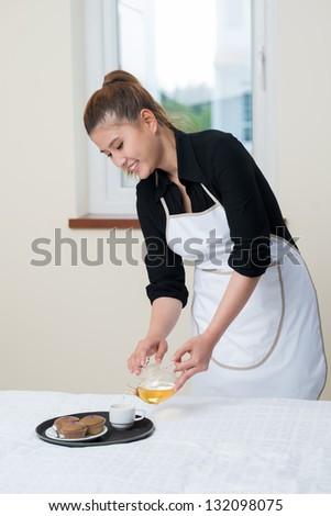 Portrait of a happy maid preparing breakfast - stock photo