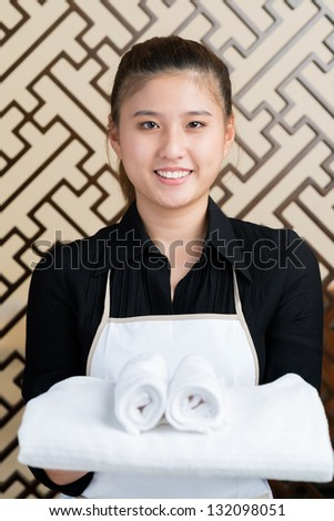 Portrait of a happy maid with towels smiling and looking at camera - stock photo