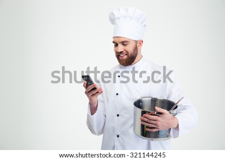 Portrait of a happy male chef cook holding pot and using smartphone isolated on a white background - stock photo