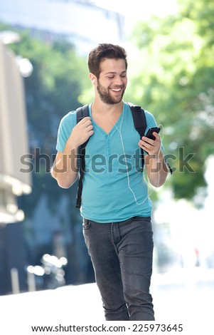 Portrait of a happy male student walking on campus with mobile phone - stock photo