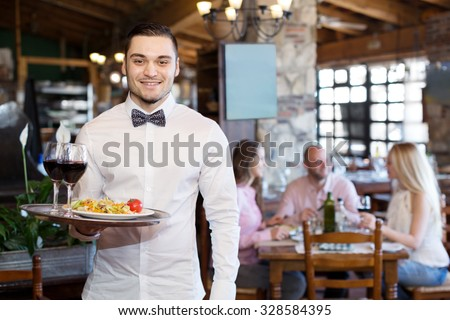 Portrait of a happy male waiter with a tray in his hand at the restaurant - stock photo