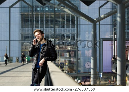 Portrait of a happy man calling by mobile phone at station - stock photo
