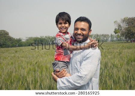 Portrait of a happy man carrying his son with wheat field in background