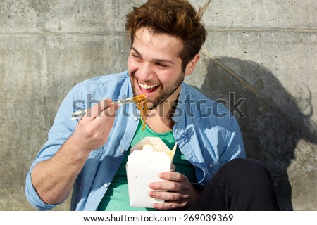 Portrait of a happy man eating food with chopsticks - stock photo