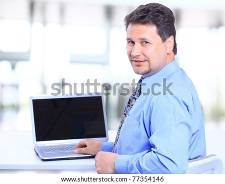 Portrait of a happy man entrepreneur displaying computer laptop in office - stock photo