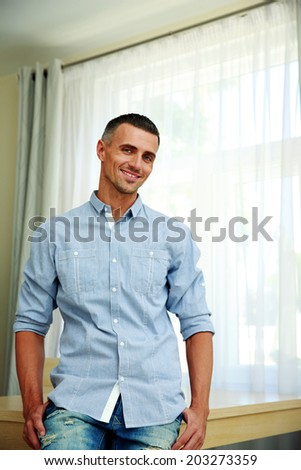 Portrait of a happy man leaning at the table - stock photo