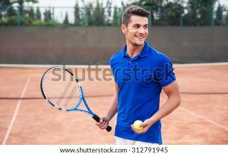 Portrait of a happy man playing in tennis outdoors - stock photo