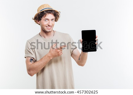 Portrait of a happy man pointing finger at tablet with blank screen isolated on a white background
