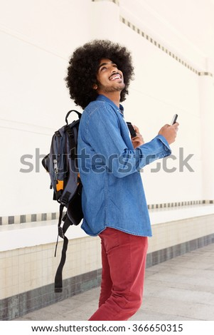 Portrait of a happy man walking with bag and mobile phone - stock photo