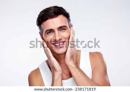 Portrait of a happy man washes over gray background - stock photo