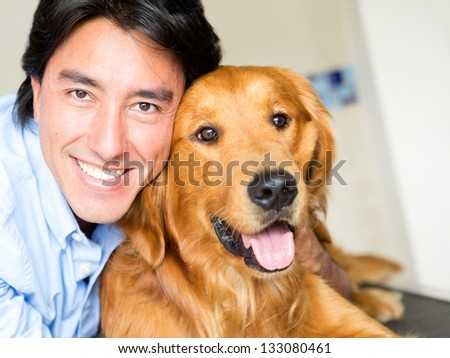 Portrait of a happy man with a dog at the vet - stock photo