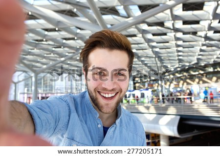 Portrait of a happy man with beard taking selfie  - stock photo