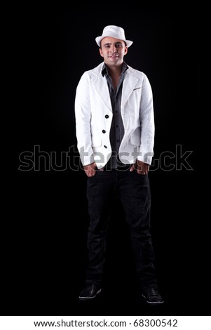 Portrait of a happy man with his white hat and coat, isolated on black. Studio shot - stock photo