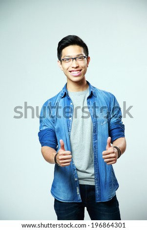 Portrait of a happy man with thumbs up on gray background - stock photo