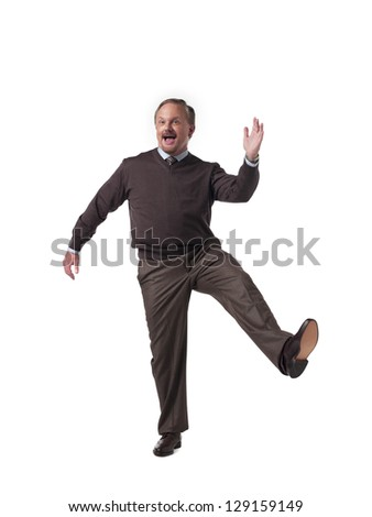 Portrait of a happy mature businessman standing on one leg over white background