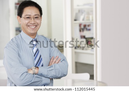 Portrait of a happy mature businessman with arms crossed - stock photo