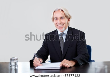 Portrait of a happy mature male entrepreneur working at the office - stock photo