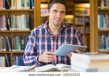 Portrait of a happy mature male student holding tablet PC in the library