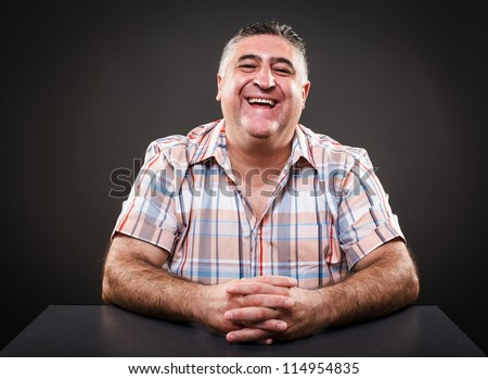 Portrait of a happy mature man sitting at table on gray background