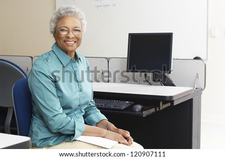 Portrait of a happy mature teacher sitting in classroom